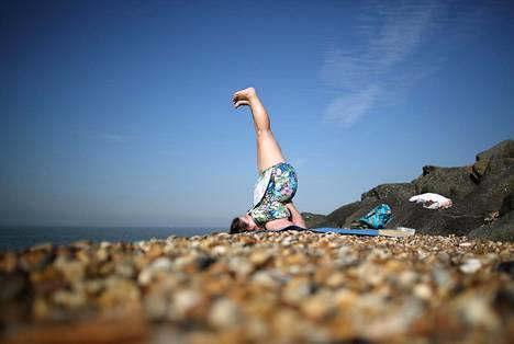 Nainen joogasi rannalla Sheernessissä Etelä-Englannissa syyskuussa 2013.