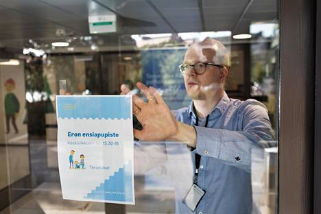 Lastenvalvoja Pekka Sipilä teippasi mainosjulistetta oveen, kun eron ensiapupiste oli avautumassa ensimmäistä kertaa Kallion perhekeskukseen.