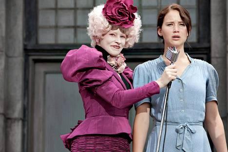 Pääkaupungin hienostoa edustava Effie Trinket (Elizabeth Banks) avustaa maalaista Katniss Everdeeniä (Jennifer Lawrence) nälkäpeleissä.