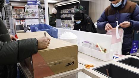 Asiakkaat postittamassa pakettejaan Postin Kasarminkadun toimipisteessä Helsingissä 15. joulukuuta 2020.
