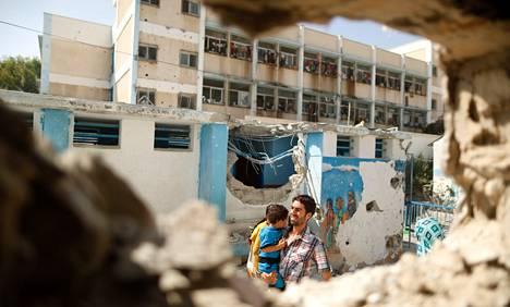 Palestiinalaismies kantoi lasta YK:n koulun pihalla Gazassa keskiviikkona. Israel iski kouluun tiistain ja keskiviikon välisenä yönä.