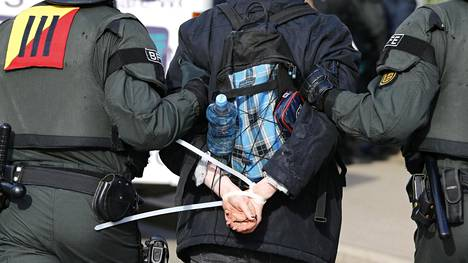 Mellakkapoliisi saattoi lauantaina Stuttgartissa mielenosoittajaa, jonka kädet oli sidottu nippusiteillä selän taakse.
