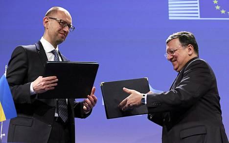 Ukrainan pääministeri Arseni Jatsenjuk (vas.) ja EU:n komission puheenjohtaja José Manuel Barroso pitelivät asiakirjoja allekirjoitettuaan taloussopimuksen Brysselissä tiistaina.