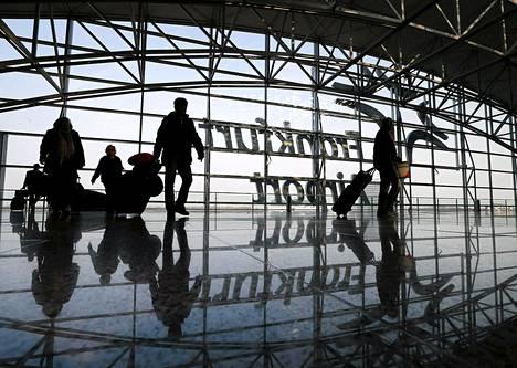 Matkustajia laukkuinen vaeltamassa Frankfurtin valtavalla lentokentällä maaliskuussa. Torstaina alkava lakko uhkaa sekoittaa Sankan lentokenttien liikenteen.