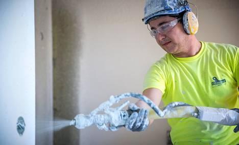 YIT:n kirvesmies Marko Pitkänen kiinnittää räystään otsalautaa Vantaan Piletti -talon katolla Tikkurilassa paahtavassa helteessä. Vuoden päästä valmistuvan talon asunnoista on myyty vajaa viidennes.