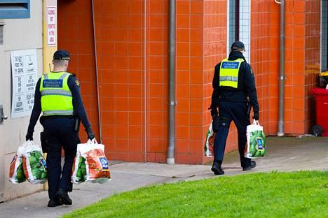 Poliisit viemässä ruokaa eristyksissä oleville asukkaille.