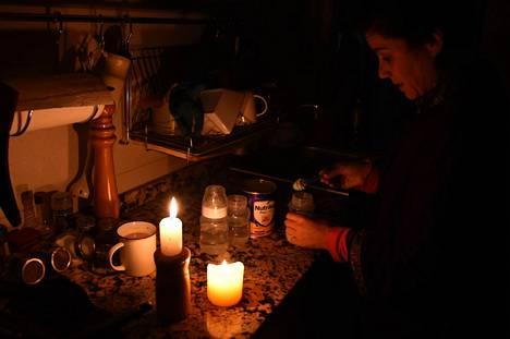 Sähkökatkosta kärsinyt uruguaylainen nainen valmisti vauvanruokaa kynttilän valossa maan pääkaupungissa Montevideossa sunnuntaina.
