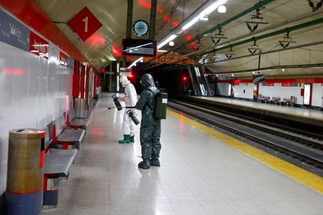 Armeijan erikoisjoukot desinfioivat Nuevos Ministeriosin metroasemaa Madridissa perjantaina.