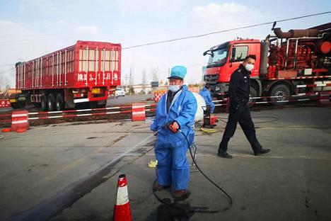 Työntekijä desinfioi tartuntatilalla käynyttä autoa Yulinissa Shaanxin maakunnassa maaliskuussa.