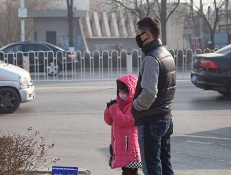 Mies ja tyttö turvautuivat hengityssuojaimiin Baodingin teollisuusalueella.