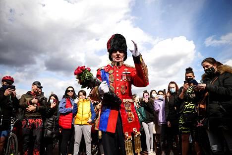 Mies toi kukkia Buckinghamin palatsin edustalle Lontoossa perjantaina.