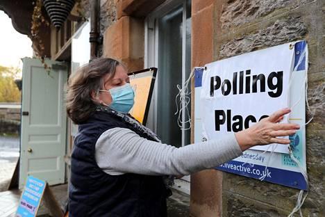 Nainen asettelee kylttiä äänestyspaikalla Pitlochryn kaupungissa Skotlannissa 6. toukokuuta 2021.