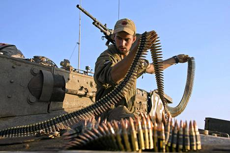 Israelilainen sotilas tarkasti Merkava-panssarivaunun konekiväärin panosvyötä Israelin miehittämillä Golanin kukkuloilla tiistaina.