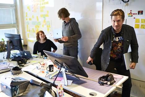 Mika Väisänen työpaikallaan Reaktorin toimistolla Helsingissä. Takana työkaverit Aino Sipilä ja Wilfried Bock.