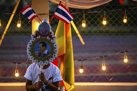 Poika piteli Thaimaan kuninkaan Bhumipolin kannatuskylttiä keskiviikkona.