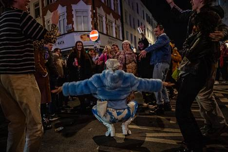 Ihmiset tanssivat keskellä katua Lontoossa.