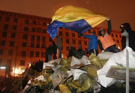 Hallitusta vastustavat mielenosoittajat heiluttavat Ukrainan lippua rakentamallaan barrikaadilla torstaina.