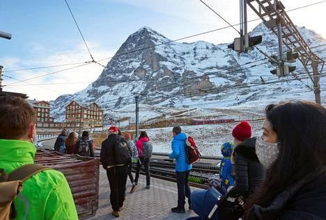 Sveitsiläisessä Grindelwaldin rinnekeskuksessa matkustajat odottivat junaa kasvomasekilla suojautuneina maanantaina.