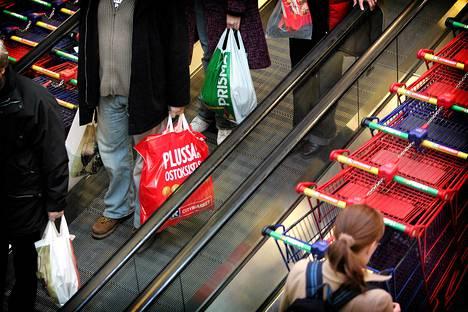 Elintarvikeliikkeen asiakkaita muovipusseineen.