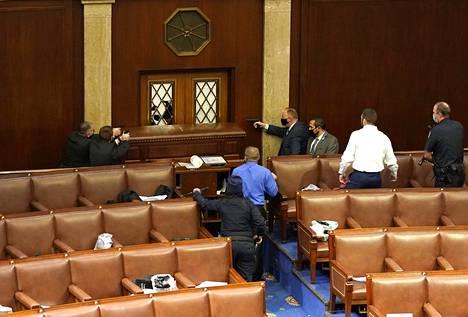 Kongressin poliisit osoittavat aseillaan istuntosali ovea, jonka lasin tunkeutujat rikkoivat.