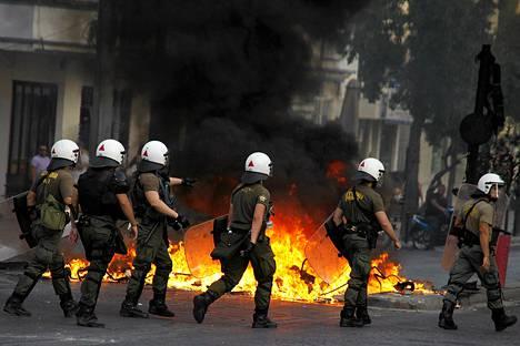 Mellakkapoliisit ottivat yhteen mielenosoittajien kanssa Ateenassa perjantaina. Protestit alkoivat lipuntarkastajaa paenneen nuorukaisen kuolemasta.