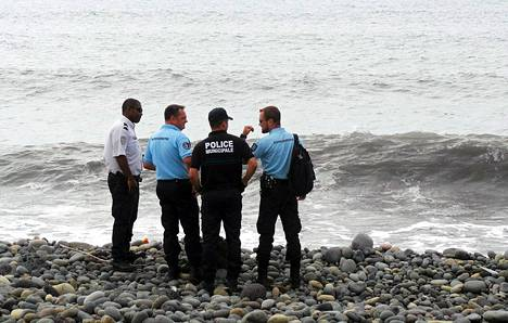 Ranskalaispoliisit seisovat Réunionin saarelta rannalla, josta lentokoneen osa löytyi.