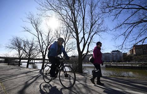Pyöräilijä ja kävelijä liikenteessä aurinkoisena aamupäivänä Hakaniemenrannassa 20. huhtikuuta 2020.