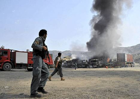 Afganistanilaiset poliisit tutkivat Naton kuorma-autoja, joihin Taleban-taistelijat iskivät Jalalabadin maakunnassa maanantaina.