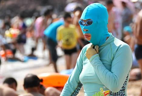 Auringonottaja käytti Face-Kini-naamaria Qingdaon satamakaupungin uimarannalla elokuussa.