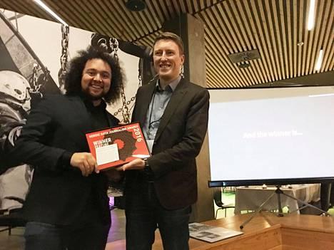 Helsingin Sanomien tuottaja Juhani Saarinen (oik.) tiimeinen voitti perjantaina pohjoismaisen datajournalismipalkinnon. Palkinnon ojensi tanskalainen Magnus Bjerg.