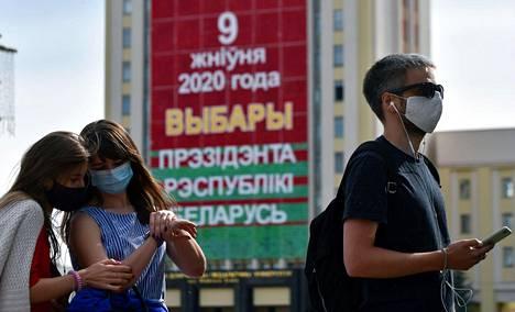 Minskin keskustassa oleva iso kyltti mainostaa valkovenäjäksi Valko-Venäjän presidentinvaaleja, joihin vallanpitäjät eivät päästäneet suosittuja vastaehdokkaita. Edessä oppositioehdokkaiden kannattajia seisoo jonottamassa jättääkseen valituksen keskusvaalilautakuntaan ehdokkaiden hylkäämisestä.