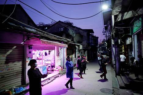 Naapuruston asukkaita tanssimassa yhdessä Wuhanin kujilla.
