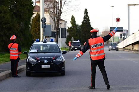 Italialaiset karabinieerit valvoivat asukkaiden liikkumista tarkastuspisteellä Milanossa 10. maaliskuuta.