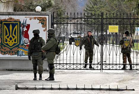 Ukrainalaissotilaat (oik.) partioivat Perevalnojen tukikohdan aidan sisäpuolella torstaina. Venäläisiksi väitettyjen joukkojen partio vartioi piiritettyä tukikohtaa aidan ulkopuolella.