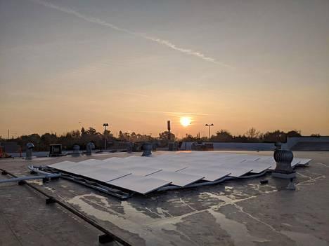 Skycool-yhtiön jäähdytyspaneeleja talon katolla Yhdysvalloissa Kaliforniassa auringonnousun aikaan.