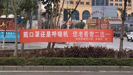 """""""Käytä maskia tai hengityslaitetta, voit valita toisen näistä kahdesta"""", lukee kiinalaisessa banderollissa."""