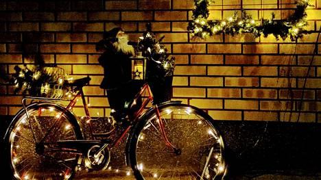 Raili Karvonen-Urhola luottaa joulukoristeissaan uusiokäyttöön: pyörä toimii kesäisin kukkatelineenä ja talvisin jouluvalokoristeena.