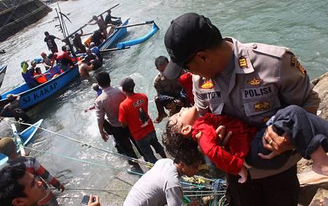 Poliisi kantoi tajutonta lasta Indonesiassa Jaavan saaren rannikolla 25. heinäkuuta. Lapsi oli mukana Australian Joulusaarelle yrittäneessä pakolaisveneessä, joka törmäsi koralliriuttaan.