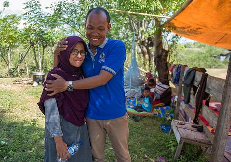 Azwan halasi vaimoaan Dewi Prasastia heidän talonsa edessä Palussa Indonesiassa maanantaina.
