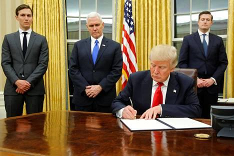 Presidentti Donald Trump allekirjoitti ensimmäiset määräyksensä Valkoisessa talossa perjantaina. Mukana olivat presidentin vävy Jared Kushner (vas.) ja varapresidentti Mike Pence (toinen vas.).