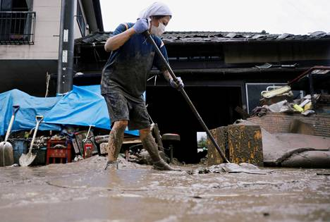 Nainen siivoamassa mutaa kotinsa edustalta torstaina Kumamoton prefektuurissa Japanissa.