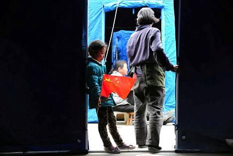 Tyttö nojasi hätämajoitusalueen teltan seinään Longmenin kylässä, joka sijaitsee lähellä maanjäristyksen keskusaluetta Sichuanin maakunnassa Kiinassa.