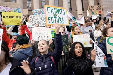 Nuoret ilmastolakkolaiset Eduskuntatalon portailla perjantaina.