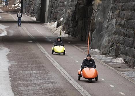 Sledgo-ajoneuvon kehittäneet Samuel Kuosmanen ja keksijä Pentti Airaksinen (takana) huristelivat sähkökäyttöisellä kulkuvälineellä Helsingin Baanalla.