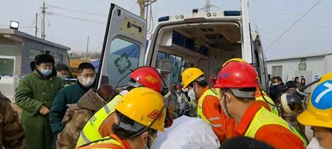 Pelastustyöntekijät kuljettivat kaivosmiestä ambulanssiin sunnuntaina 24. tammikuuta Qixiassa Shandongin maakunnassa.