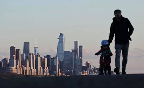 Vanhempi ja lapsi ulkoilivat auringon laskiessa New Yorkissa 9. huhtikuuta.