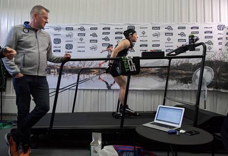 """Matti Haavisto (vas.) seurasi sykelukemia, kun Krista Pärmäkoski teki viime lokakuussa rullasuksiharjoitusta oman """"treeniluolansa"""" matolla Lahdessa."""