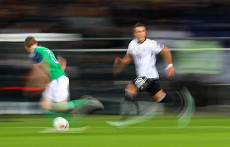 Saksan Mario Götze (oik.) juoksee Pohjois-Irlannin pelaajan rinnalla jalkapallon MM-kisojen karsintaottelussa Hannoverissa.