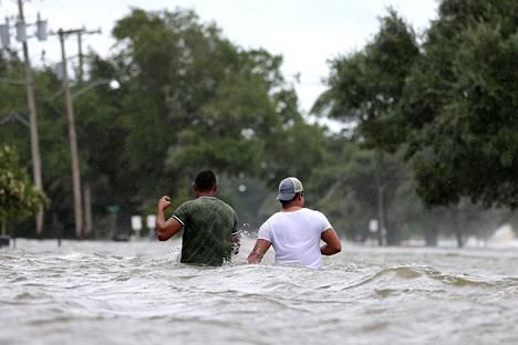 Ihmiset kahlasivat tulvivalla kadulla Barry-hirmumyrskyn jälkeen Mandevillessa Louisianassa lauantaina.