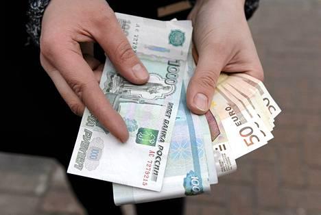 Moskovalainen nostamassa ruplia pankkiautomaatilla Arbat-kävelykadulla Moskovassa torstaina 18. joulukuuta 2014.
